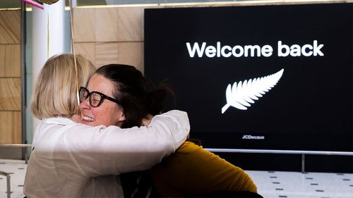 New Zealand travellers embrace at Sydney International Airport.