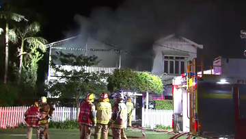 A fire has ravaged an inner-city Brisbane home overnight, with fire crews battling to stall the multi-story inferno from affecting nearby houses.