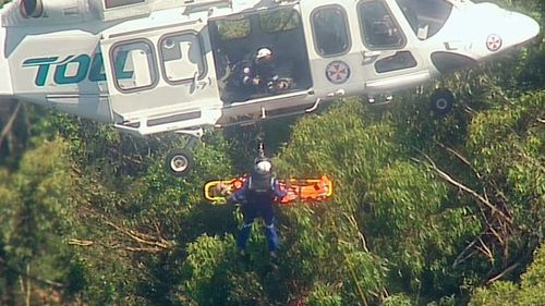 Specialist paramedics winch the injured man from heavy cover into the helicopter.