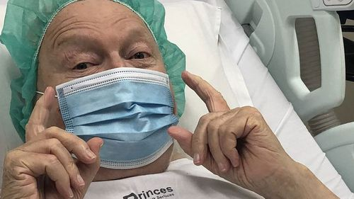 A masked Bert Newton in his hospital bed.
