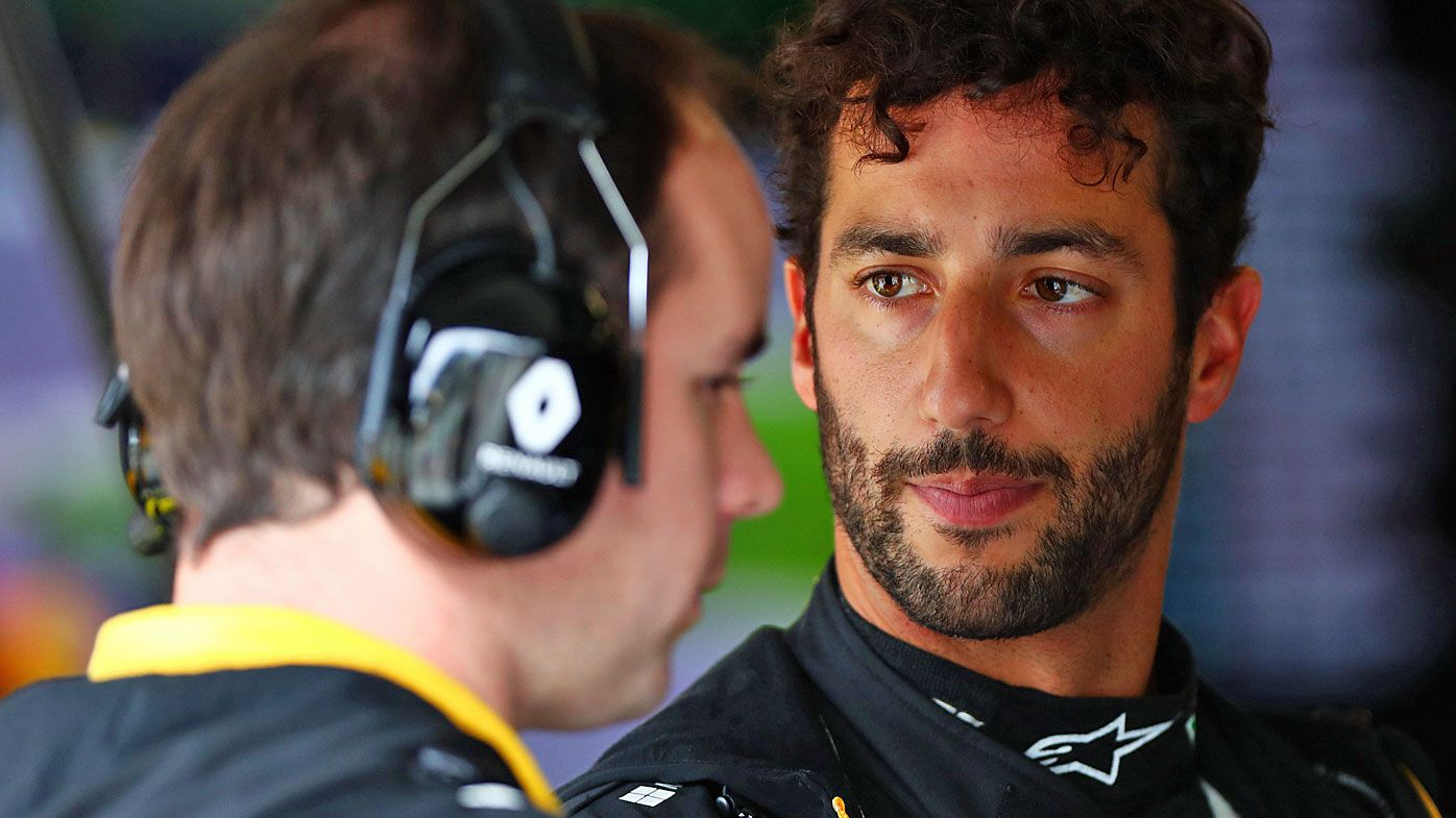 Daniel Ricciardo talks with a Renault Sport F1 team member in the garage