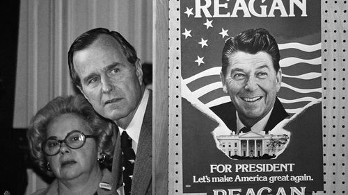 In this March 4, 1980 file photo, George H.W. Bush and an unidentified woman peek around a partition with a poster of Ronald Reagan.