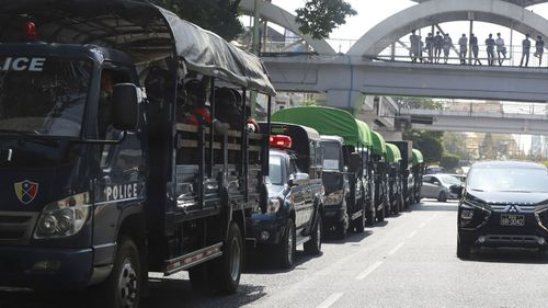 Policemen sit inside trucks parked on a road in the downtown area of Yangon, Myanmar.