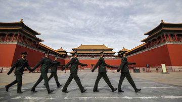 Masked soldiers march past the Forbidden City in Beijing.