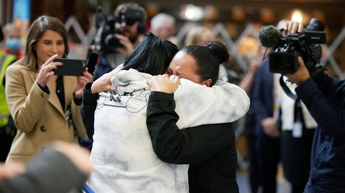 People embrace as they are reunited at Auckland International Airport in Auckland yesterday.