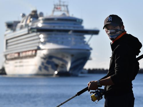 A fisherman wearing a face mask looks on as the Ruby Princess, with crew only onboard, docks at Port Kembla, Wollongong.