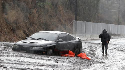 A man walks by a car that was caught in a mudslide on Topanga Canyon Boulevard after heavy rains in Topanga, California. (AAP)