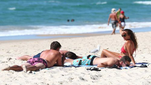 People relax on the beach at Burleigh Heads on the Gold Coast.