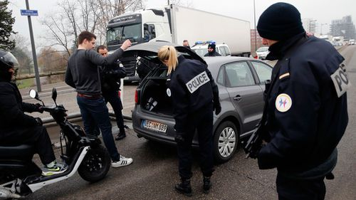 Police search cars at the France/German boarder.