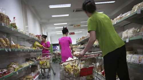 Staff at the Potonggang department store stock shelves with local and imported snacks. (AAP)