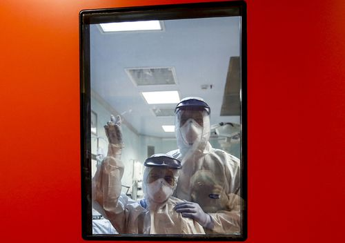 Medical staff wave from inside the ICU unit of the Covid 3 hospital in Casalpalocco, near Rome.