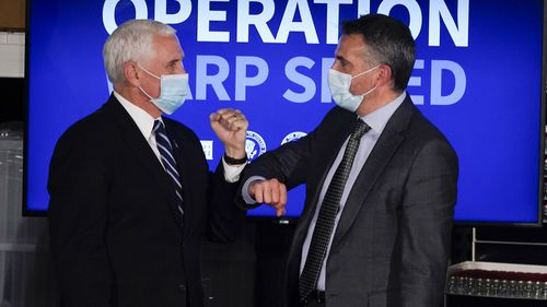 In this Dec. 15, 2020, photo, Vice President Mike Pence elbow bumps Alessandro Maselli, President and Chief Operating Officer at Catalent, following a round table discussion at Catalent Biologics in Bloomington, Ind