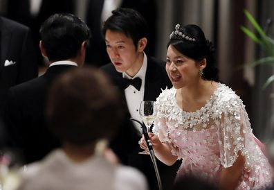 Japan's former princess Ayako Moriya (R) and her husband Kei Moriya (C) toast with Crown Prince Naruhito at their wedding banquet in Tokyo, Japan, October 28, 2018.