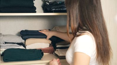 Woman organizing clothes in wardrobe