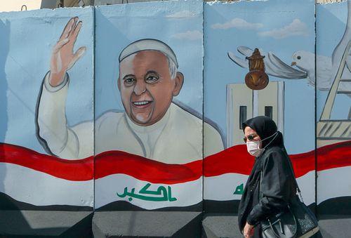 Seorang wanita berjalan melewati mural yang menggambarkan Paus Fransiskus di dinding beton yang ditempatkan oleh pasukan keamanan Irak untuk mengelilingi Gereja Our Lady of Salvation selama persiapan kunjungan Paus di Baghdad, Irak, Senin, 1 Maret 2021