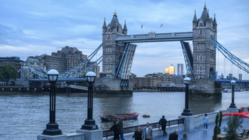 Tower Bridge is seen stuck in the raised position as people walk along the south bank on August 9, 2021 in London, England. Tower Bridge, London's 127-year-old iconic landmark, has become stuck open after a technical failure, causing major traffic issues in the capital.