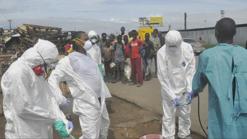 Onlookers watch as health workers in protective gear spray each other with disinfectant in Monrovia, Liberia. (AAP)