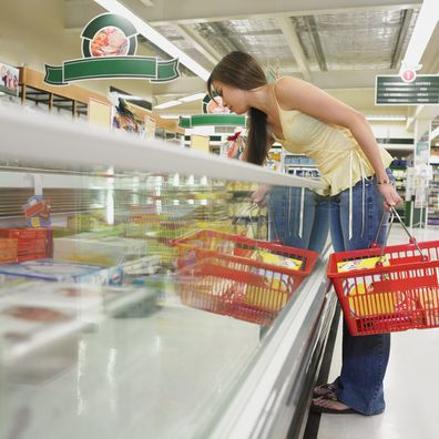 Woman grocery shopping holding a basket