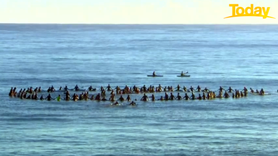 Dozens of Byron Bay locals assembled in the surf to form a 'cancel' symbol.