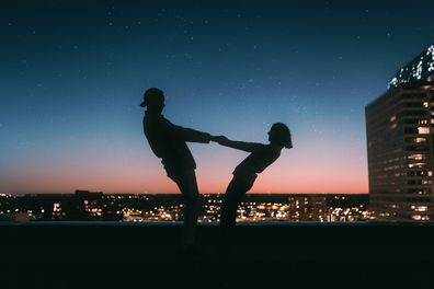 Couple holding hands at sunset on top of city