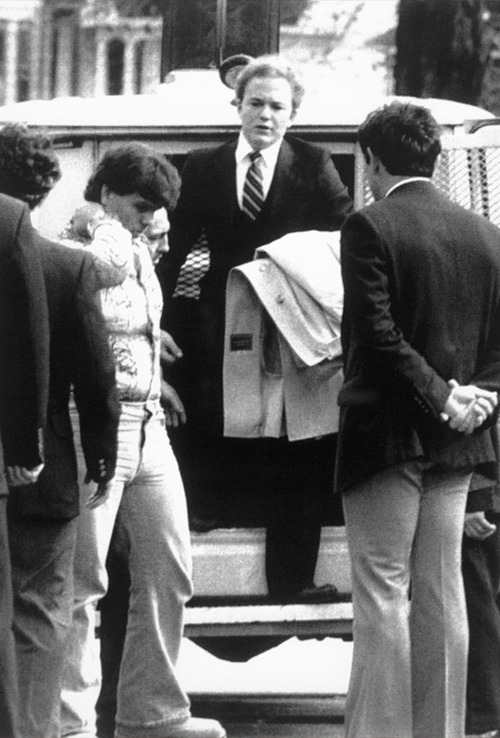 Arne C. Johnson, with a coat over arm, steps from a police van on arrival at court in Danbury for the opening day of his trial.