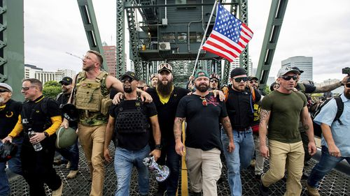 Members of the Proud Boys and other right-wing demonstrators march across the Hawthorne Bridge during a rally in Portland last year. The group includes organiser Joe Biggs, in a green hat, and Proud Boys Chairman Enrique Tarrio, holding the megaphone.