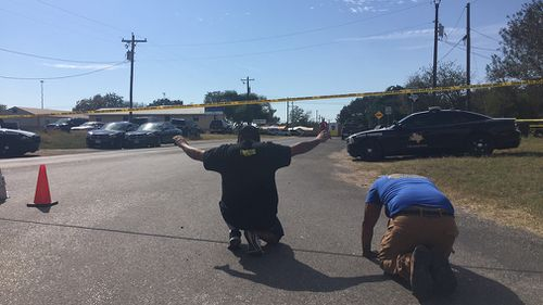 Two community members pray on the edge of the crime scene. (Lizzie Pearl)