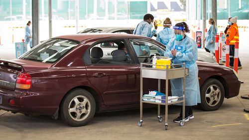 A nurse administers the Pfizer COVID-19 vaccine at a drive through vaccination centre in Melton, Melbourne.