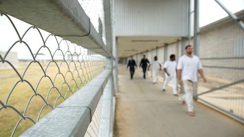 Staff escort prisoners through a prison in Australia.