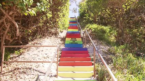 This colourful staircase has become the centre of a war of words in a Queensland beach town.
