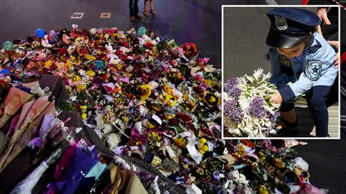 Floral tributes at the scene, and a child dressed in a police costume lays a bouquet. (AAP)