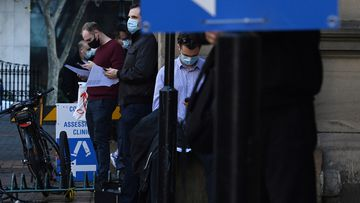 People wearing face masks wait in a queue at a COVID-19 testing site located at the Sydney Eye Hospital.