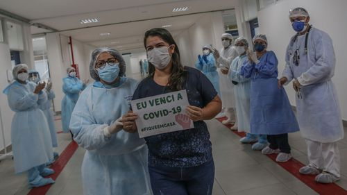 "After 10 days of treatment for coronavirus, Kelly Araujo de Andrade holds a sign that reads ""I beat the COVID-19 #StayAtHome"" while she walks through the main hall followed by a chief nurse leaving the Gilberto Novaes Municipal Field Hospital, in Manaus, Brazil."
