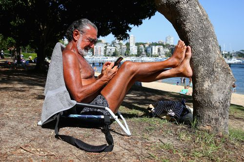 Ed Sciberras relaxes in the shade at Red Leaf Beach, in Sydney, this afternoon.