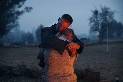 Phillip Harvey embraces his daughter Arianne Harvey as they stay warm beside a fire in Paradise, California.