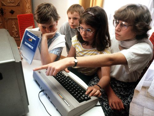 Adolescents try out a Commodore 64 in Nuremberg in May 1985. (Photo by Karl Staedele/picture alliance via Getty Images)