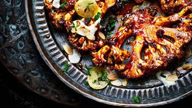 Charred cauliflower steak with tahini, harissa honey sauce and preserved lemons