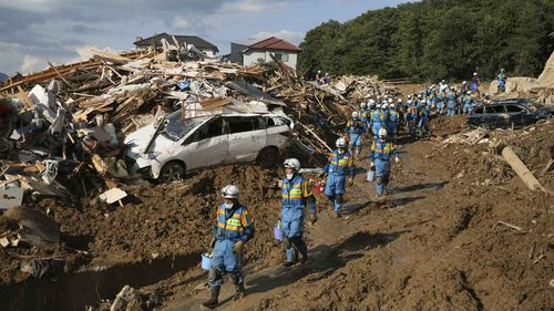 Policemen conduct a search operation for missing people in Kumano Town, Hiroshima Prefecture. (AAP)