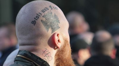 "A right-wing anti-immigration demonstrator with a head tattoo reading ""proud and free""."