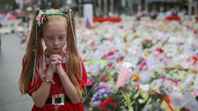 A young girl dressed in Christmas attire walks around the thousands of floral tributes.
