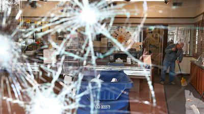 A worker cleans up glass at a business that was damaged during the first day of rioting in Ferguson. (Getty Images)