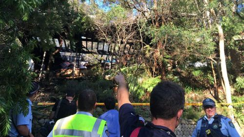 Police and emergency services surround the gutted house. (9NEWS)