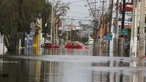 Cars trapped on a flooded street in San Juan. (AAP)