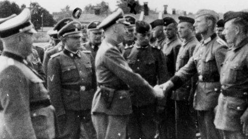 This 1942 photo provided by the United States Holocaust Memorial Museum, shows SS chief Heinrich Himmler, centre left, shaking hands with new guard recruits at the Trawniki concentration camp in Nazi occupied Poland.