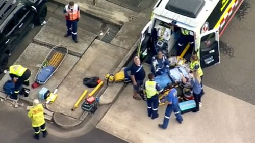 A woman is fighting for life after getting trapped underneath a rolling car.