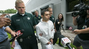 Marion County Sheriff's detectives escort a handcuffed and shackled Sky Bouche, 19, to a waiting patrol car. (AP)