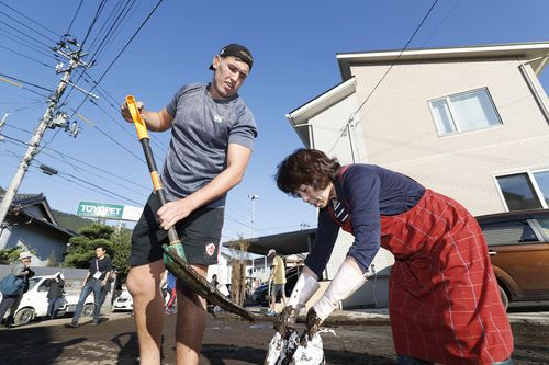 Canadian rugby player Josh Larsen, left, helps a resident to clean a road in Kamaishi, Iwate prefecture, Japan, following the cancellation of their Rugby World Cup Pool B match against Namibia due to Typhoon Hagibis.