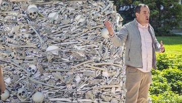 Yale epidemiology professor Gregg Gonsalves, spoke by a twelve-foot tall pile of artificial human bones at a vaccine equity demonstration.