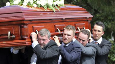Pallbearers from left, Gregory Hughes, Aaron Finch, Corey Ireland and Tom Cooper carry the coffin of Australian cricketer Phillip Hughes to the hearse. (AAP)