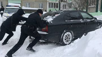 Police in Chernihiv help a car get moving in deep snow.